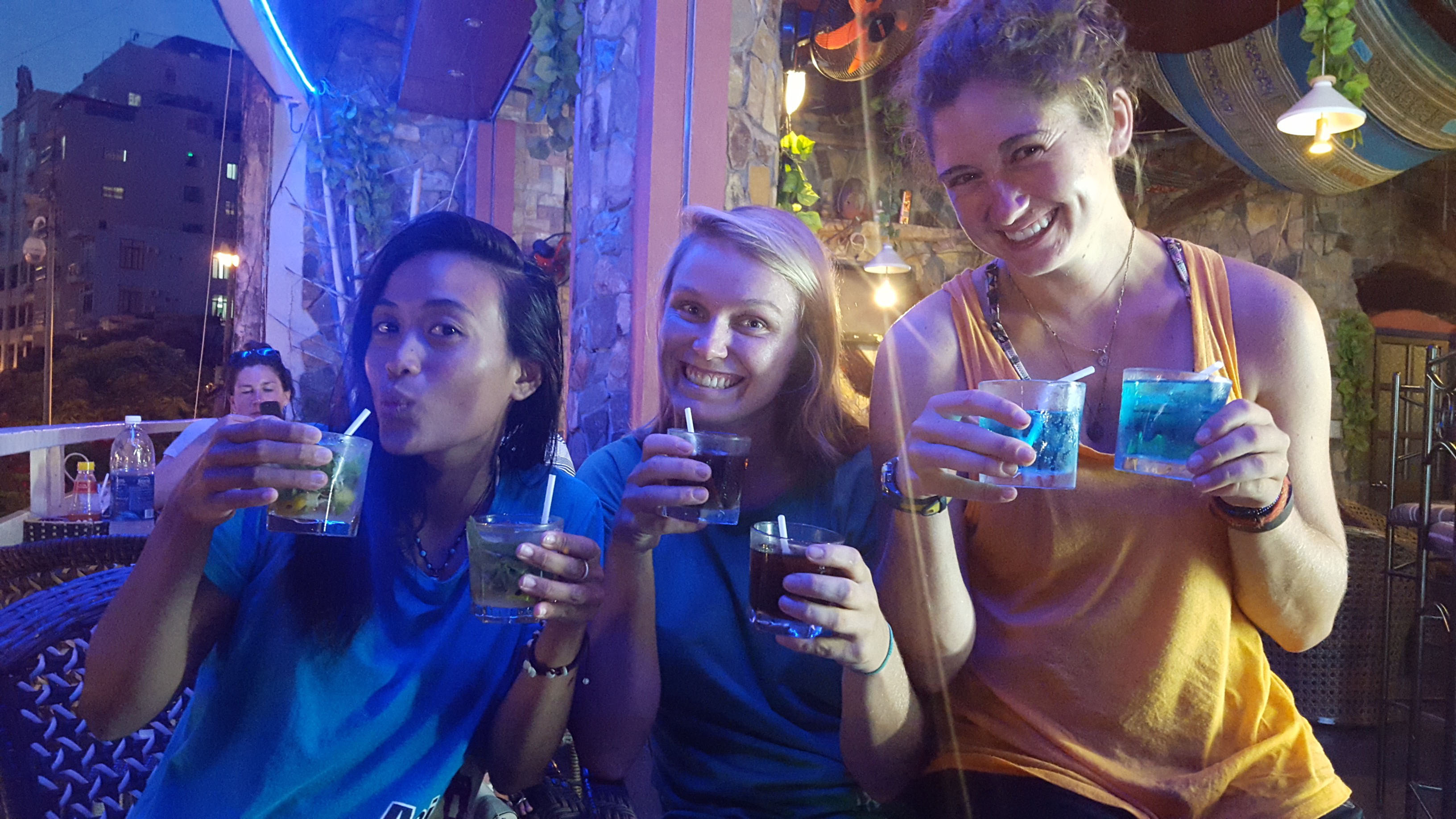 Three rock climbing and kayaking adventure guides enjoying drinks after work in Vietnam on a roof top bar.