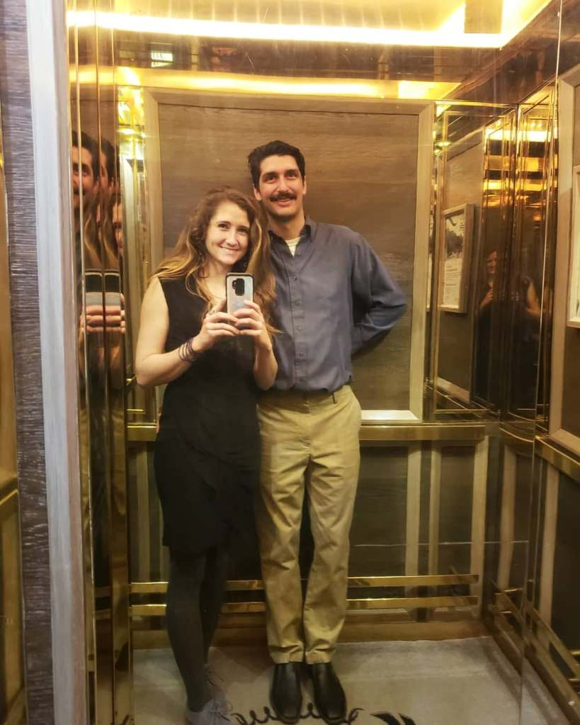 The author and her boyfriend take a photo in the gold mirror of the elevator at the Fairmont Le Chateau Frontenac in Quebec, Canada.